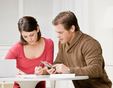 Determined couple using calculator to pay monthly bills